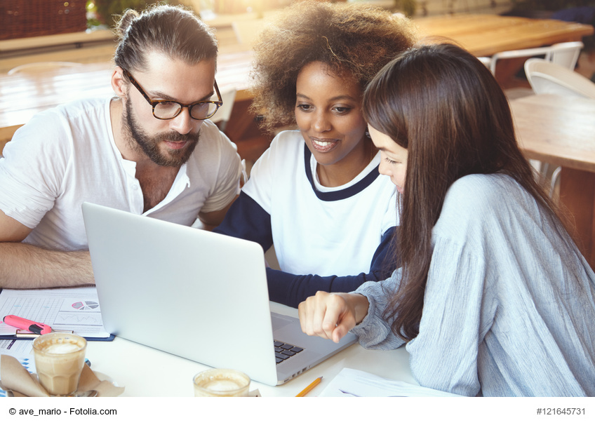 Brainstorm concept. Multiethnic group working at cafeteria, developing business strategy using laptop computer, looking concentrated. African girl showing presentaion to her partners on notebook